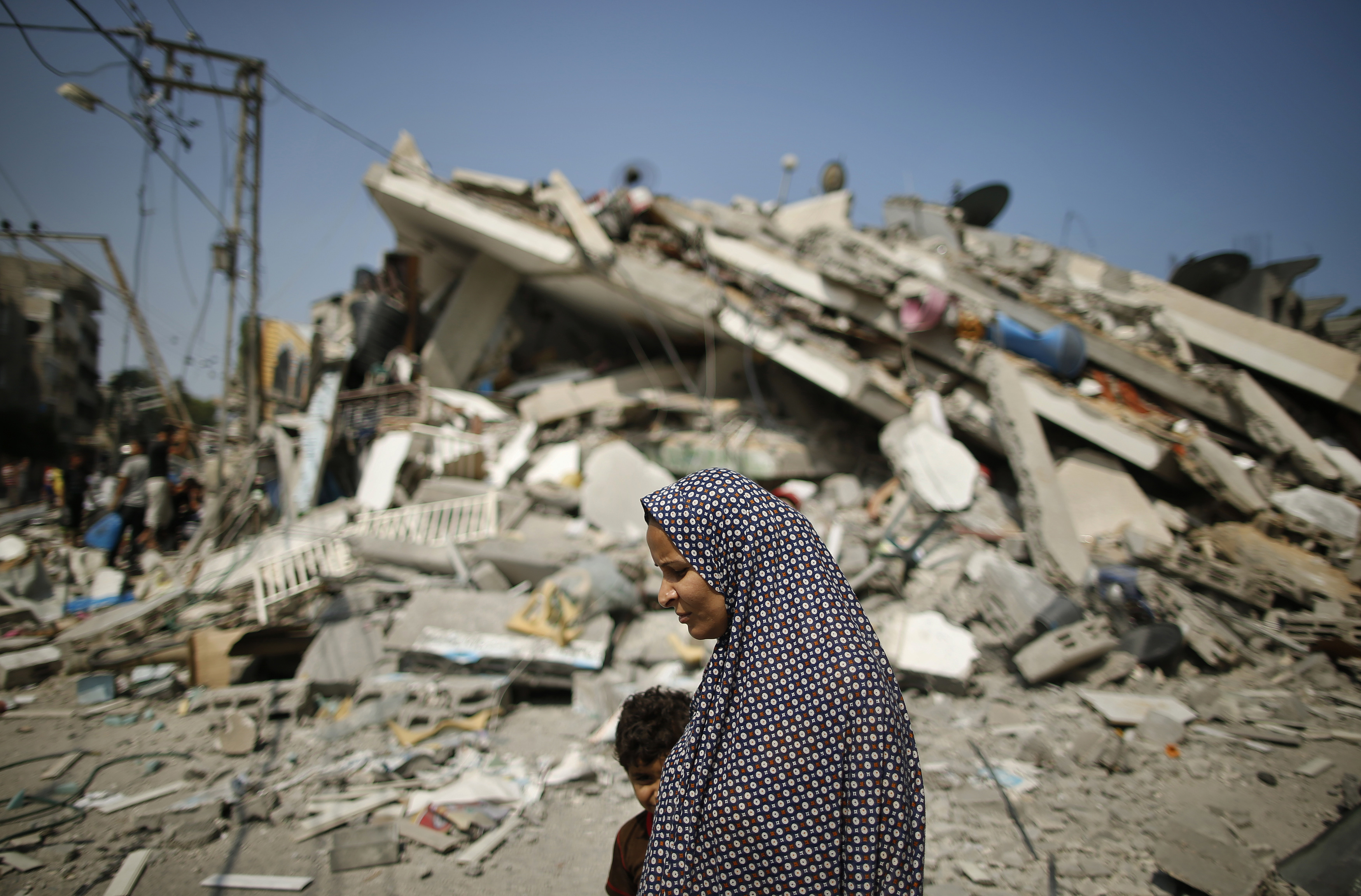 A Palestinian woman walks past the rubble of a residential building, which police said was destroyed in an Israeli air strike, in Gaza City
